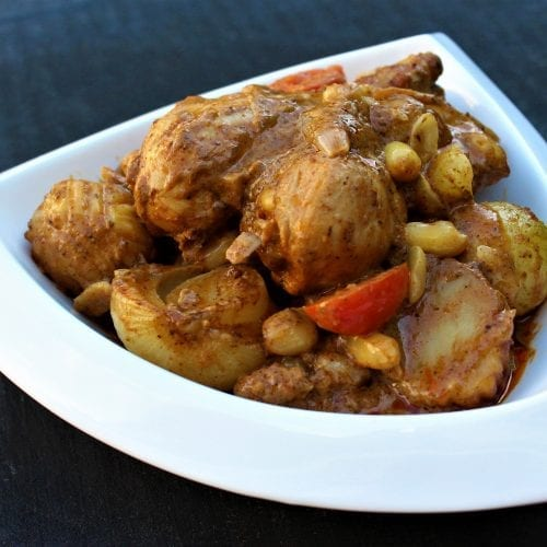 Mae Jum Thai Massaman curry cooked with chicken drumsticks, potatoes, cherry tomatoes, roasted peanuts in a white bowl